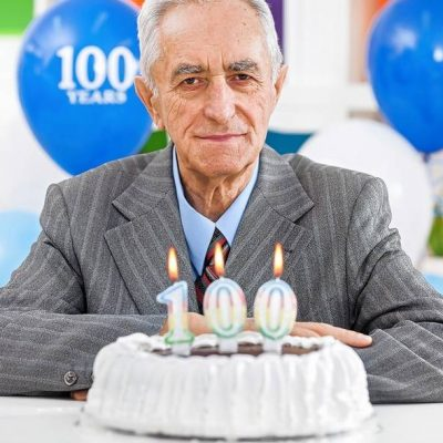Healthy 100 year old man with birthday cake